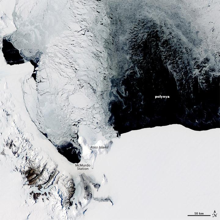 Fotografia aérea do Mar de Ross na Antártica. As porções sólidas do continente estão cobertas por gelo branco e ocupam a maior parte da imagem. No canto inferior esquerdo, é possível ver um relevo mais rugoso, indicando morros. As porções de água são da cor preta e quase um quarto da imagem é representada por uma polínia.