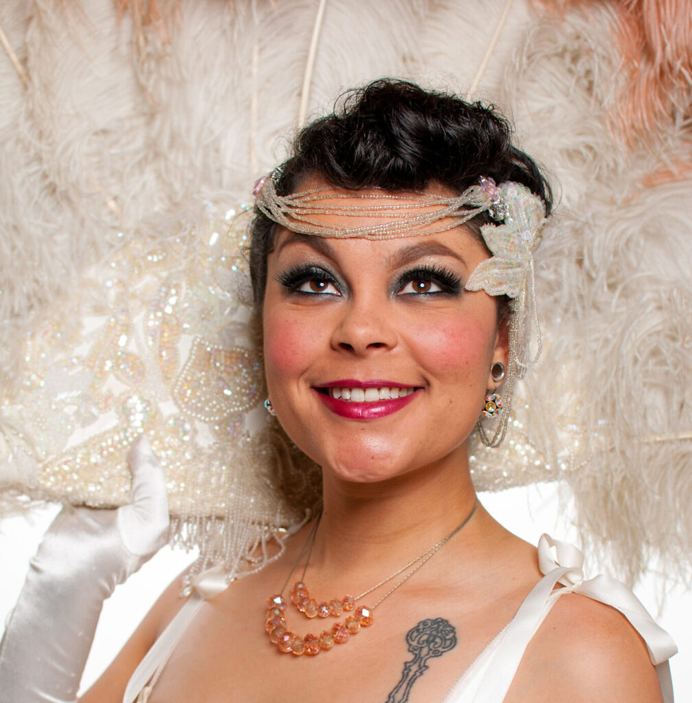 Burlesque performer Nona Narcisse is pictured from the shoulders up, wearing white straps, an amber and silver necklace, white satin gloves, and a white pearl headdress, with pink-red lipstick and glimmery blue eyeshadow. She holds a pearl-embellished feather fan behind her. She is looking up and smiling with joy, a visible key tattoo underneath her left shoulderblade.