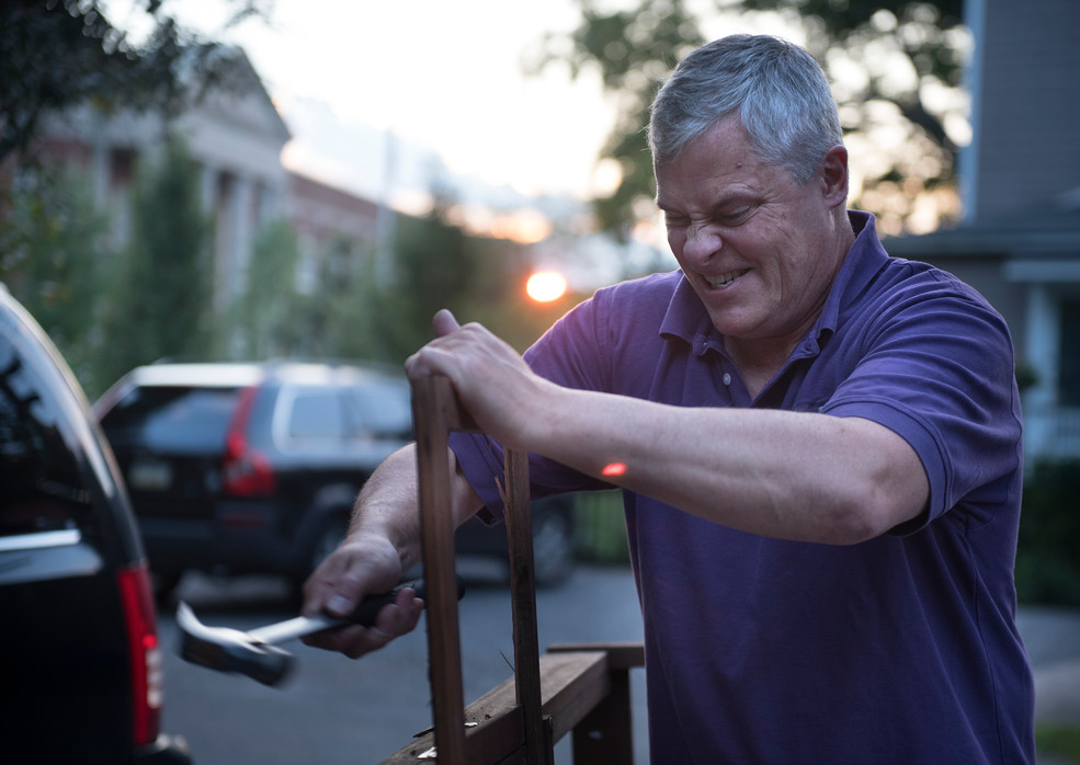 """Don McKee, from Sewickley, hammers out wooden slats from an old double lounge chair to be the frame of the cart for his Flugtag team's flying device on Monday, July 31, 2017 at Rob Riker's home in Sewickley. The team, the """"Peng-Wings,"""" will be competing in the Flugtag as part of the EQT Pittsburgh Three Rivers Regatta. (Haley Nelson/Post-Gazette)"""