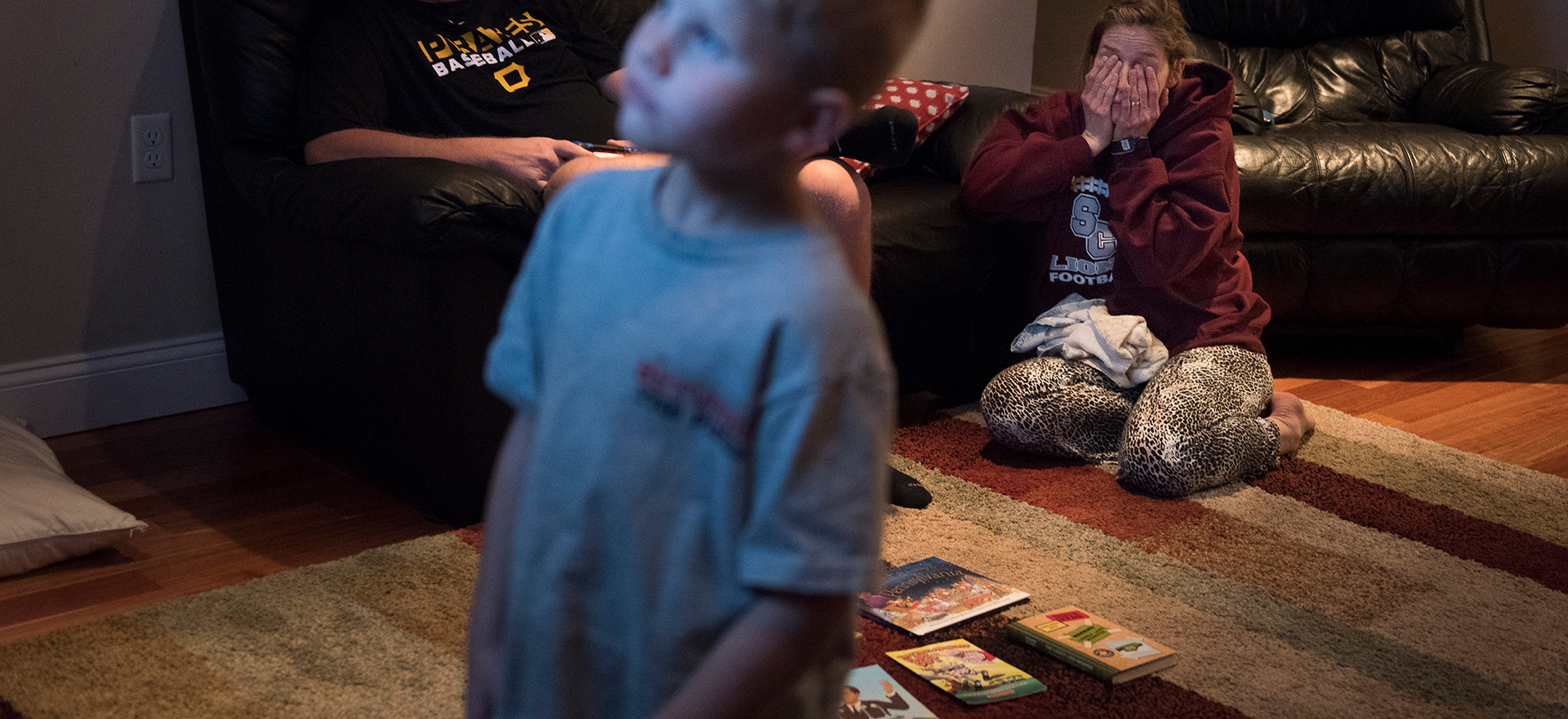 Jamie rubs her eyes as she waits for her husband, Brian, to finish playing video games with their son, Layton, so he can squeeze her head to ease the pain of her headache. In the evenings, Jamie's headaches worsen to the point that her eyes water so she uses an ice pack and pressure for relief.