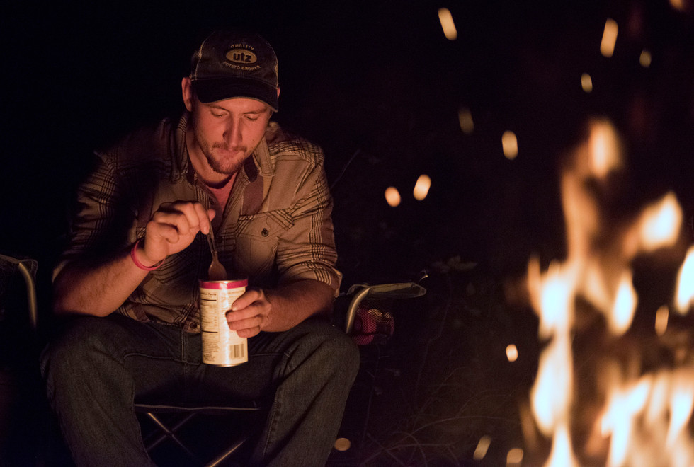 Troyer eats a can of cold beans in front of a campfire by his tent at Meyer Dairy Farm. For about half of the fall semester, his diet mainly consisted of canned beans, canned tuna, and bottles of milk from Meyer Dairy.