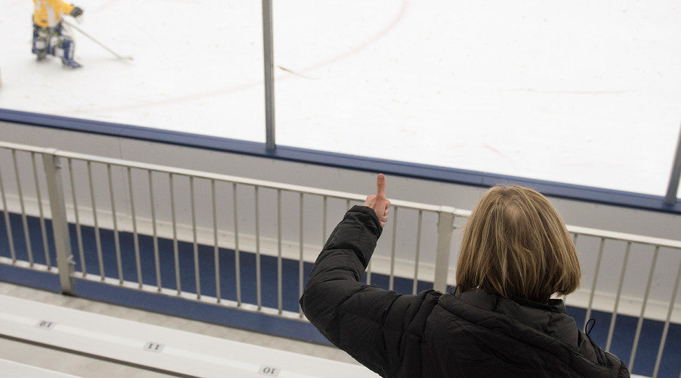 Jamie gives her son, Layton, a thumbs up during hockey practice at Pegula Ice Arena. Not all of her hair has grown back since her radiation treatment.