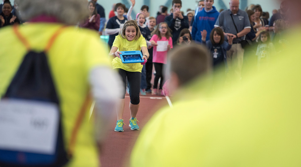 Jamie Barbarich holds out a tablet to lead a student from her special needs class down the track at the Special Olympics held at the Penn State Horace Ashenfelter III Indoor Track. Jamie is passionate about working with special needs kids and has continued to go to work at Mount Nittany Elementary School through the ups and downs of her health.