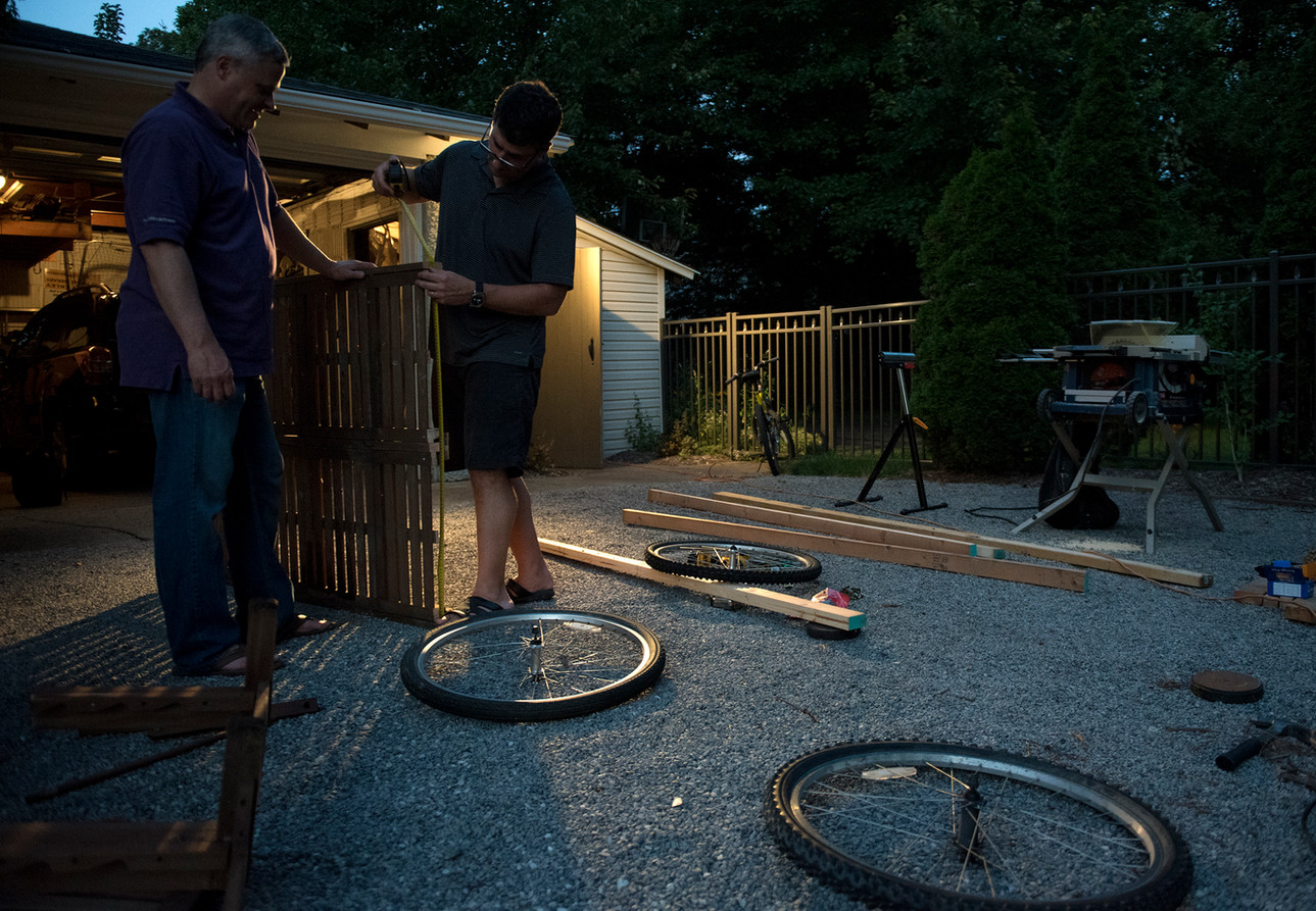 Don McKee, left, and Rob Riker work on the cart portion of their flying device on Tuesday, August 1, 2017 at Rob Riker's home in Sewickley. (Haley Nelson/Post-Gazette)