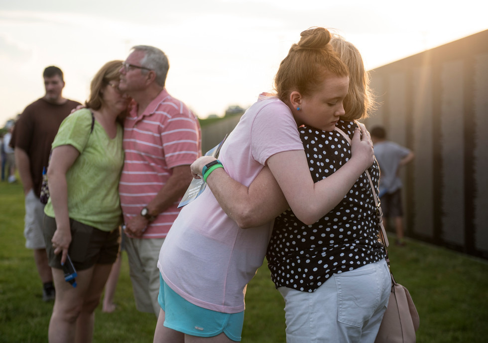 Paige Vitanza embraces her grandmother, Barbara Phelps, right, and Heather Vitanza embraces her father, Patrick Phelps at the Traveling Vietnam Memorial Wall on Thursday, June 29, 2017 at Hampton Community Park in Allison Park. Patrick served from 1970-1971 in the Vietnam War. (Pittsburgh Post-Gazette)