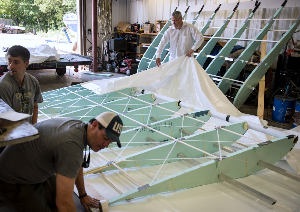 From left: Rob Riker, Andy Peacock, from McCandless, and Don McKee, prepare a wing for a shrink wrap coating for their aircraft on Tuesday, August 1, 2017 at Dockside Marine Services, Inc. in Aliquippa. (Haley Nelson/Post-Gazette)