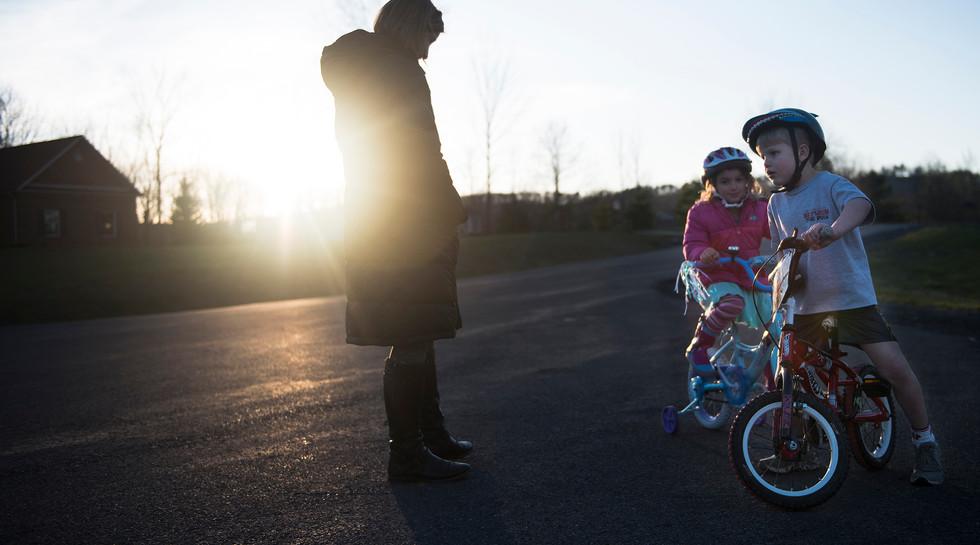 Jamie watches over as Layton and their neighbor, Sarah Riccomini, ride their bikes in the cul-de-sac.
