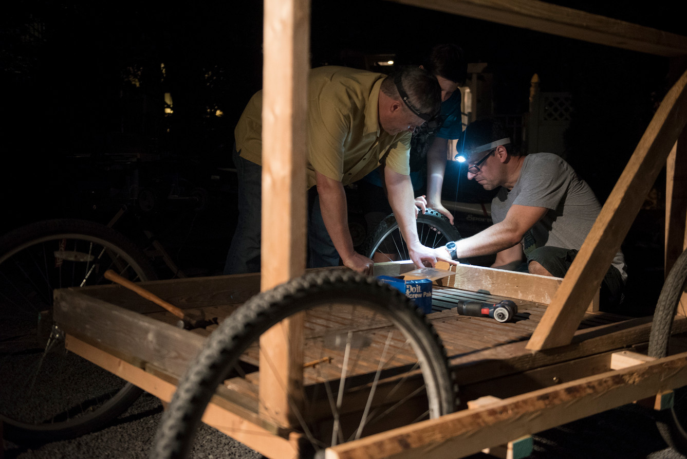 From left: Don McKee, his son, Will, and Rob RIker work on the cart portion of their flying device on Tuesday, August 1, 2017 at Rob Riker's home in Sewickley. (Haley Nelson/Post-Gazette)