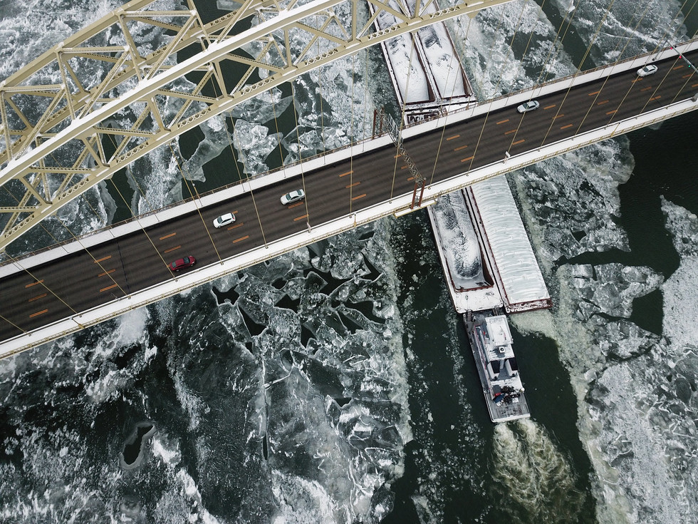 A barge cuts through ice on the Ohio River as it passes beneath the West End Bridge on Monday, Jan 1, 2018 beside the North Shore. (Pittsburgh Post-Gazette)