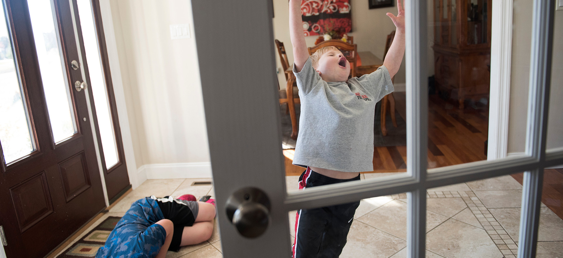 Layton Covol, 6, celebrates scoring a goal on his brother, Braylan, 10, in the foyer of their home.