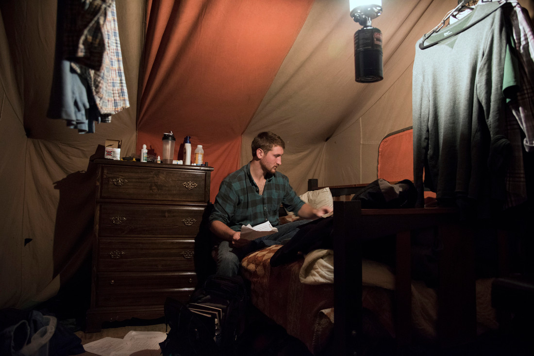 Troyer arranges his school papers in his tent. He did most of his schoolwork on campus where he has access to electricity.