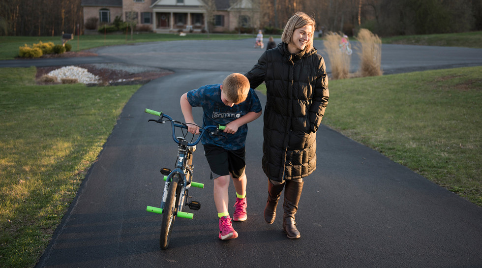 Jamie Barbarich, 36, walks with her son, Braylan Covol, up the driveway to their home in State College, Pa.