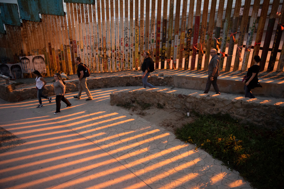 Saint Mary's College professors from left: Rebecca Anguiano, Caroline Doran, Michael Barram, John Ely, Norrie Palmer, and Maria Luisa Ruiz walk along the primary border wall just after sunset in Friendship Park on July 10, 2018 in Tijuana, Mexico. (Saint Mary's College)