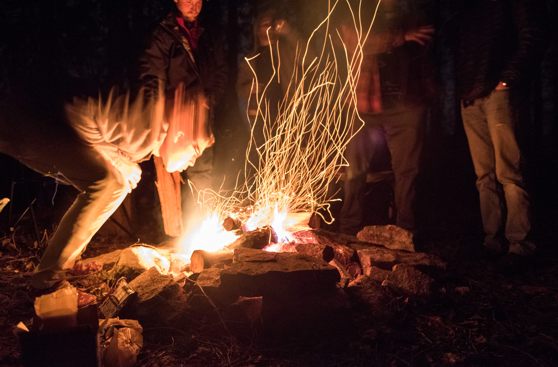 Matt McWilliams blows on the fire to stoke the flames in the stand of woods on the Meyer Dairy Farm with Troyer and some of his other firends from his hometown, Waterford, Pa. on December 5, 2015. The group came down to State College to visit Troyer at his tent in the woods on one of his last weekends living on the farm.
