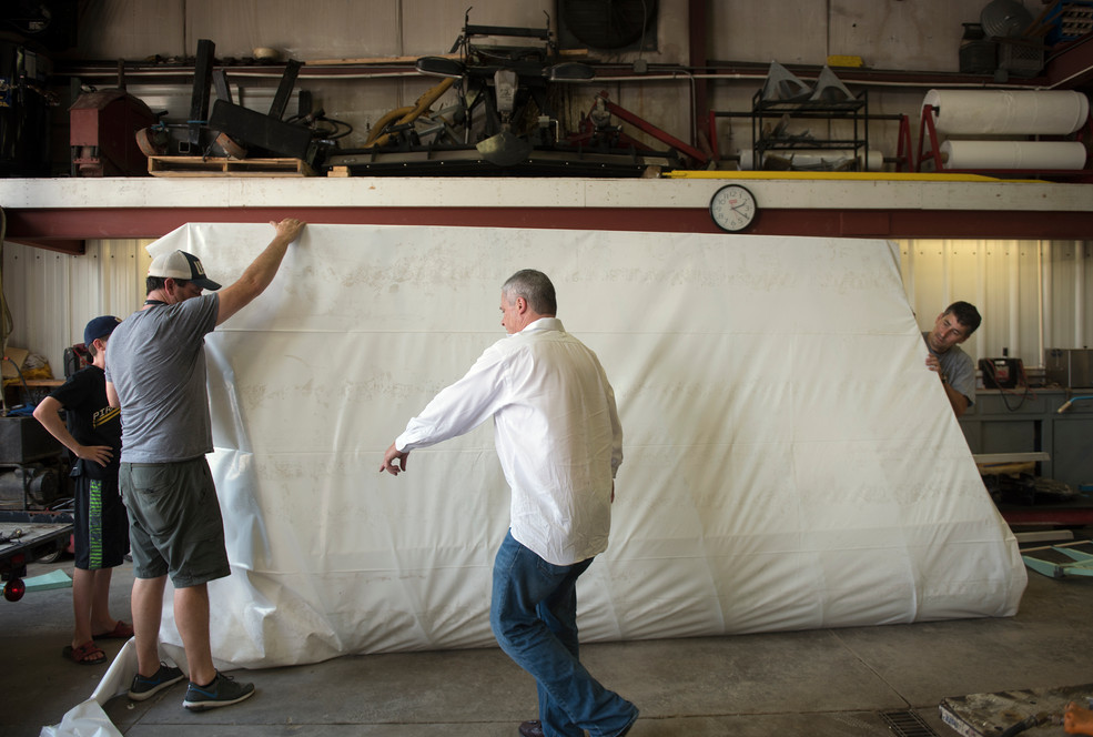From left: Ryan Peacock, and his father, Andy, Don McKee, and Rob Riker prepare a wing for a shrink wrap coating for their aircraft on Tuesday, August 1, 2017 at Dockside Marine Services, Inc. in Aliquippa. (Haley Nelson/Post-Gazette)