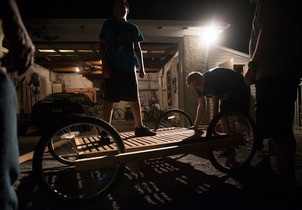 Will McKee tests out the newly-constructed base for the cart portion of the flying device on Tuesday, August 1, 2017 at Rob Riker's home in Sewickley. (Haley Nelson/Post-Gazette)