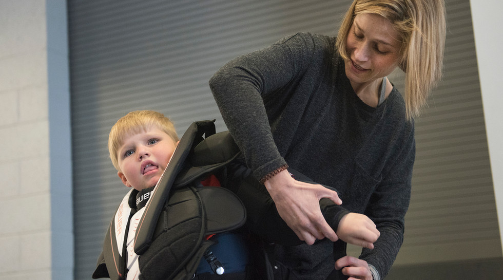 Jamie Barbarich struggles to get her son, Layton Covol, into his hockey goalie gear before practice at the Pegula Ice Arena at Penn State University.