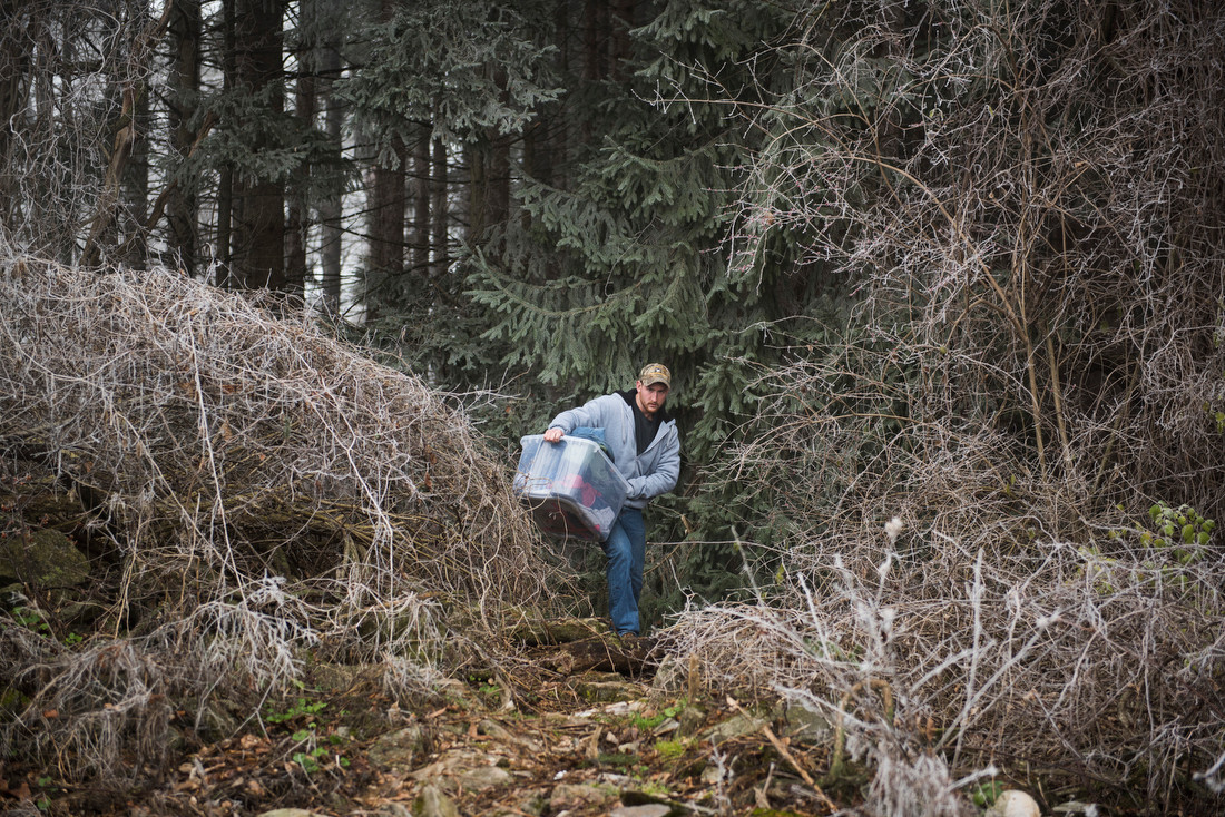 Troyer carries his laundry out of the frost-covered woods where his camp is set up to his car. He brought his laundry into town to wash it at a laundromat. As for his own personal hygiene, Troyer showered at the gym on campus.