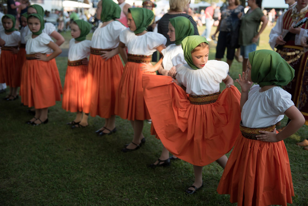 Adelina Simco, second from right, with the Trafford Junior Tamburitzans, plays with her skirt before a performance at the 58th Annual International Village on Tuesday, August 15, 2017 at Renziehausen Park in McKeesport. (Pittsburgh Post-Gazette)