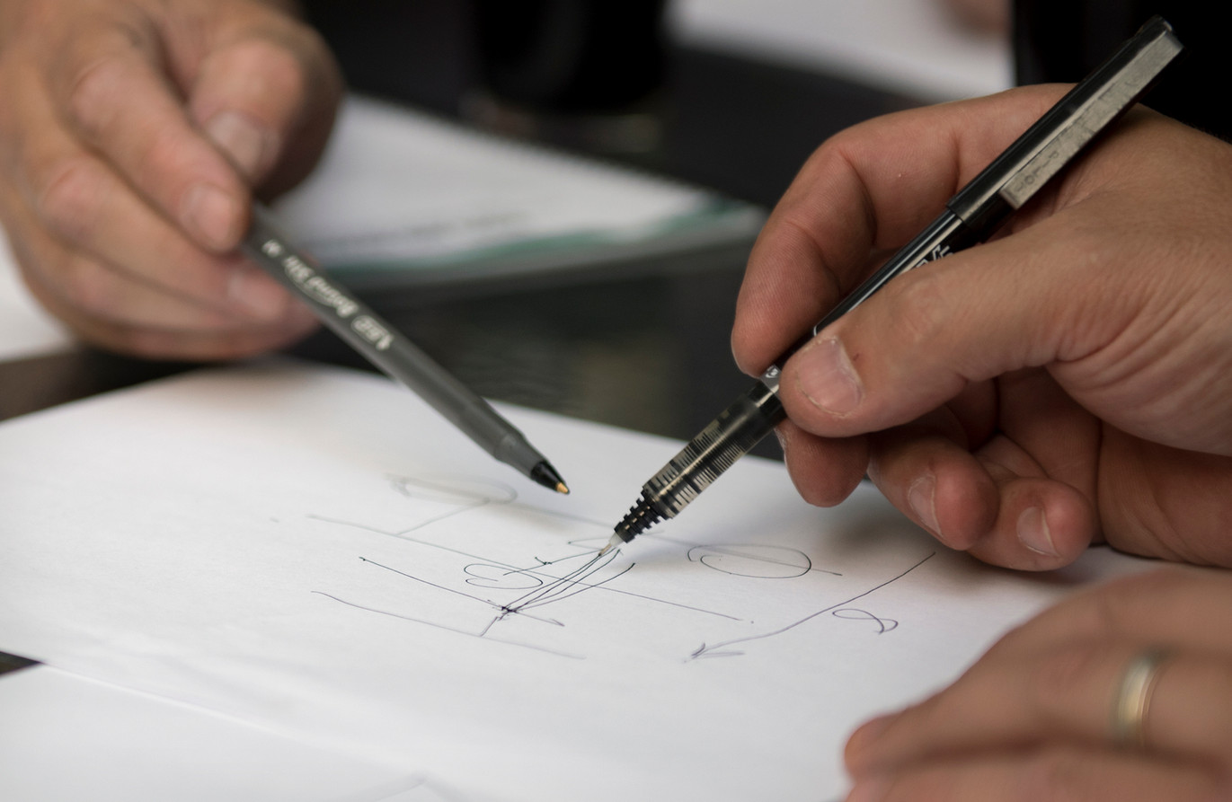 Don McKee, left, and Rob Riker draw out a sketch for the cart portion of their flying device on Monday, July 31, 2017 at Rob Riker's home in Sewickley. (Haley Nelson/Post-Gazette)