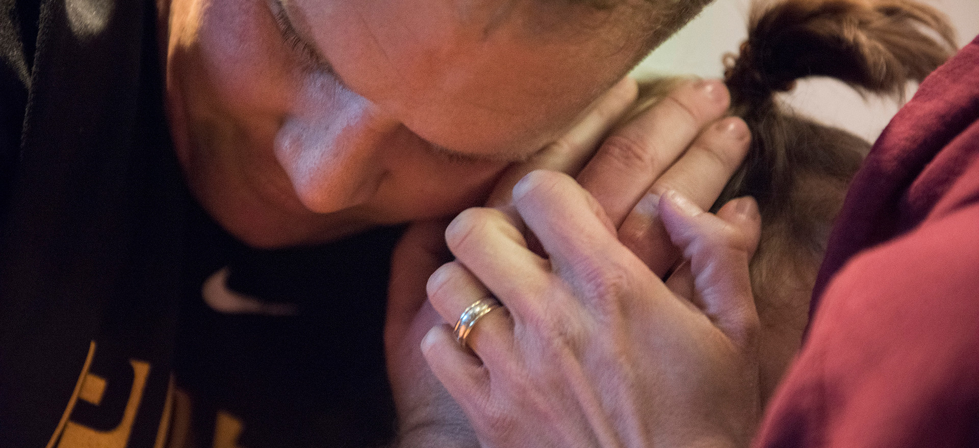 Brian Covol squeezes the head of his wife, Jamie Barbarich, in order to ease the pain of her headache.