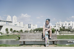 Male skater sitting on a park bench