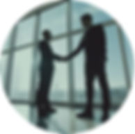 Silhouette of two man shaking hands in front of large window