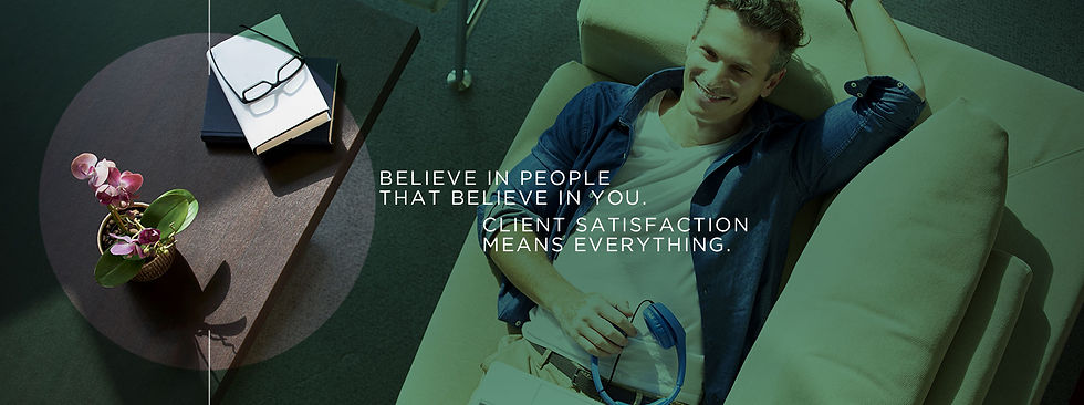 Young man relaxing on a couch smiling. A sign reads: Believe in people that believe in you. Client satisfaction means everything.