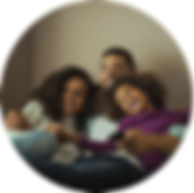 Ayoung couple with young daughter sitting on a couch. Father holding a TV remote