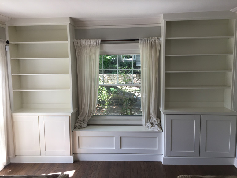 Custom built window seat with bookcases on either side and cabinet storage