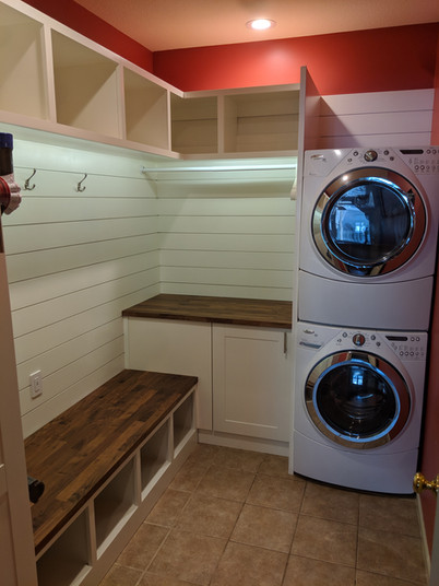 Laundry room built-in with custom shelving, shiplap accent wall, and bench with storage space below