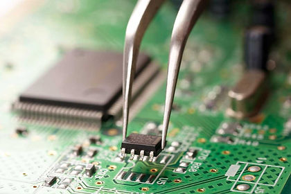 tweezers placing an IC onto a motherboard
