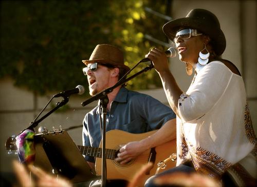 A Black female musician sings while a white guitarist accompanies her.