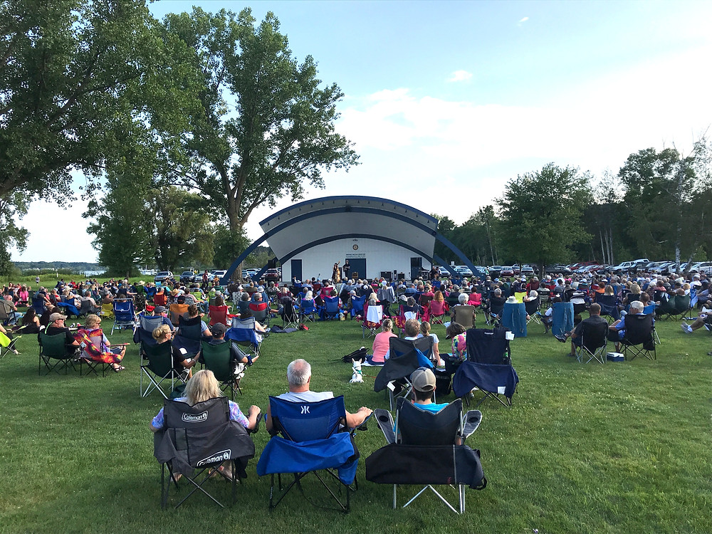 A large crowd is gathered outside for a Free Summer Concert, hosted by the ACWL-Nuveen