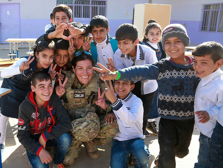 SGT Tracy McKithern poses with Kurdish children in Erbil, Iraq.