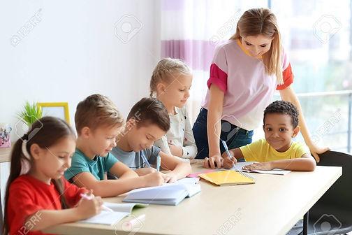 99820516-female-teacher-helping-children