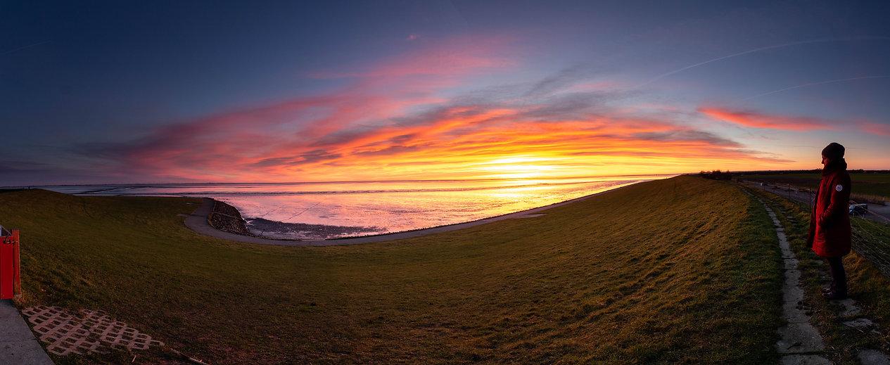 Schöner Sonnenuntergang am Deich der Nordseeküste und Wattenmeer in Nordfriesland