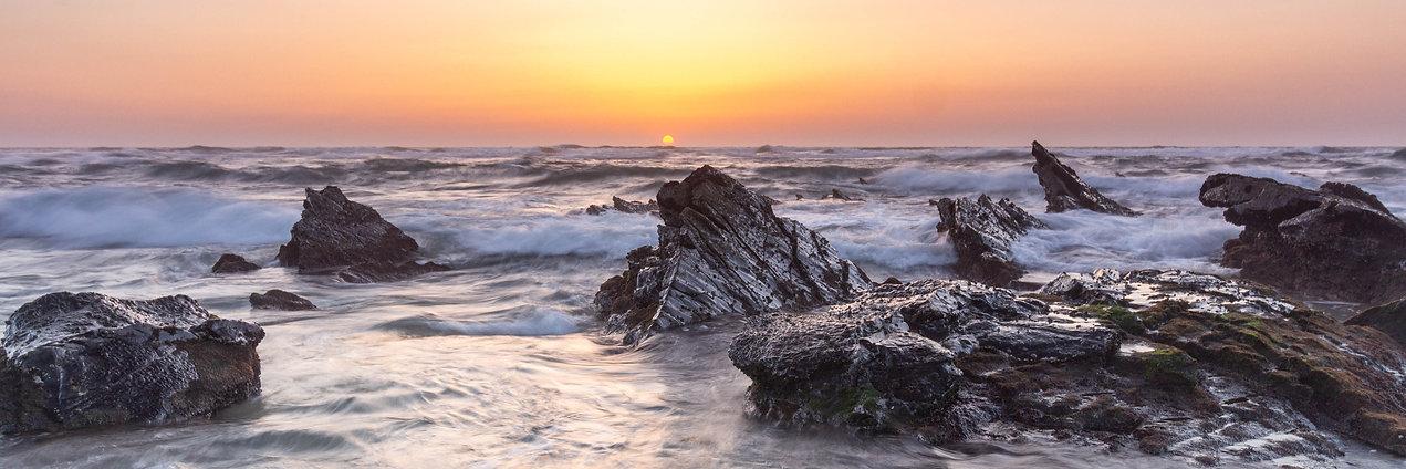 Sonnenuntergang mit Brandung und schroffen Steinen in der Algarve Portugal