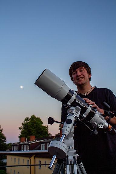 Yannick Jorzik-Brzelinski mit Teleskop und Vollmond im Hintergrund