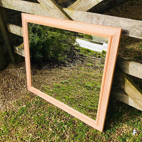 Modern bevelled edge mirror with leaf pattern moulded frame.