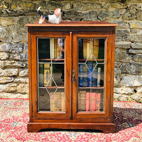 Antique freestanding bookcase with lead worked astragal glazed doors.