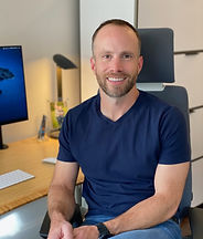 Joe Charat sitting at his desk, smiling, wearing a blue shirt and jeans.