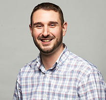 A headshot of Jay Signorello, wearing a plaid shirt, smiling, with a plain grey backdrop.