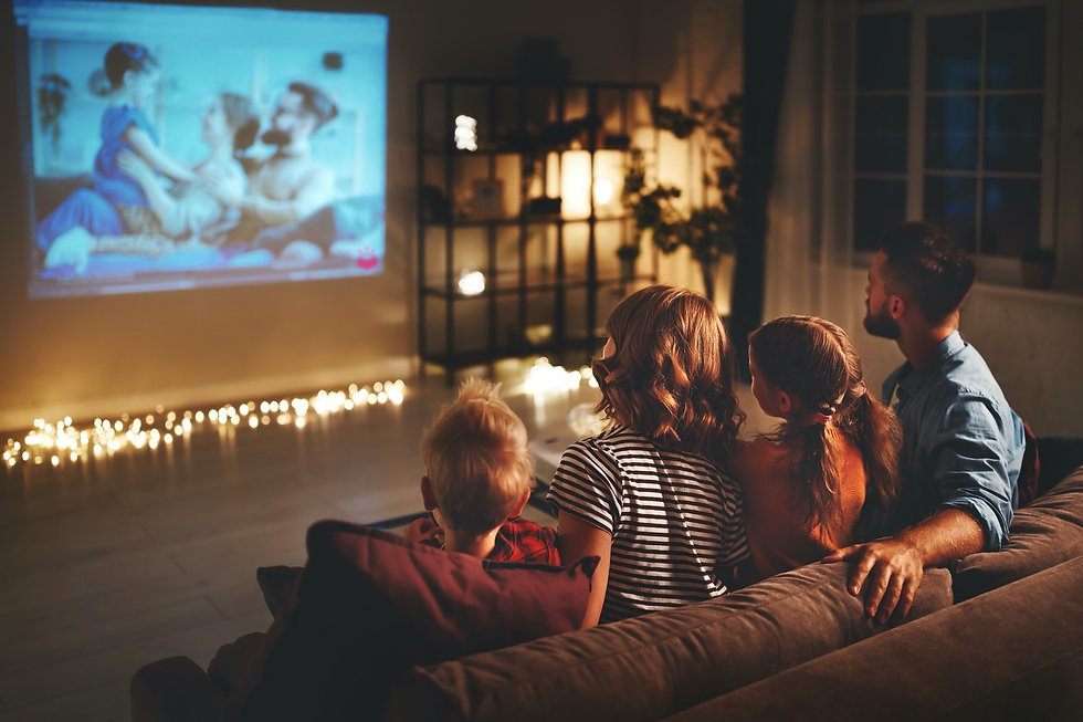 A family of four reminiscing by watching a Backstory slideshow projected onto their living room wall.