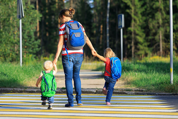 A mom, with her back facing the camera, crosses a street while holding her two toddler's hands. They're wearing backpacks.