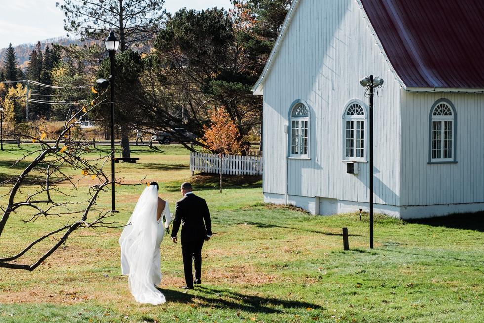 Photo de mariage au soleil, en octobre, devant la chapelle de Mont-Tremblant