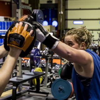 brunette female in gym sparring