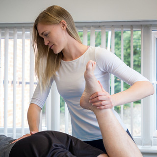 blonde physio treating patient for lower back pain