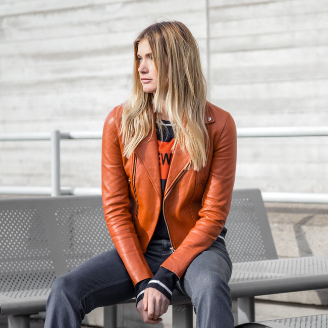 blonde model sat on table wearing flares and an orange leather jacket