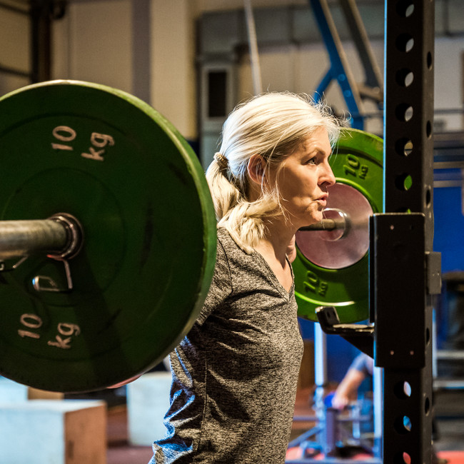 grey haired lady at squatting rack